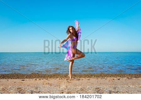 Young beautiful lady with curly hair posing with pareo on the beach against blue sky and sea background