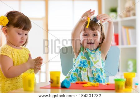 Little kids have a fun together with colorful modeling clay at daycare. Creative toddlers molding at home. Children girls play with plasticine or dough.