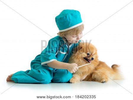 Kid weared doctor clothes playing veterinarian with dog