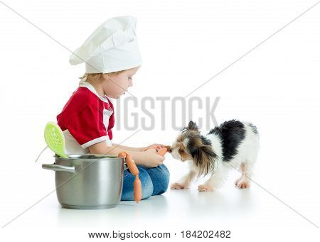 Role-playing game. Kid boy playing chef with dog. Child weared cook feeds hungry puppy.