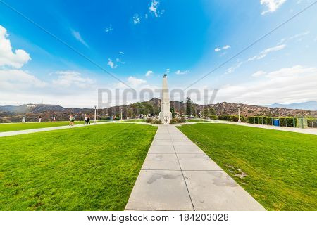 Los Angeles CA USA - Obelisk in Griffith park with Hollywood sign in the background
