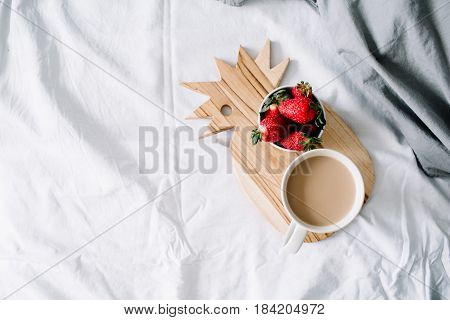 Breakfast in bed with coffee mug and strawberry. Bright grey linens. Flat lay top view.