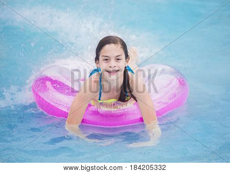 Beautiful young girl playing in the pool in summer time
