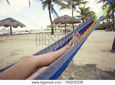 Beautiful female feet and legs relaxing in a blue hammock on the beach. Colorful toenails and peaceful tranquil scene at a tropical beach resort in the Caribbean