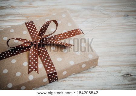 Box In Craft Paper, Eco Paper On The Wooden Table. Top View. Brown Paper Wrapped Gift Box With Satin