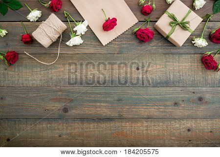 Frame with roses, gift box, craft paper and twine on wood background. Flat lay, top view. Woman background