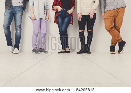 Casual young people. Crop of diverse informal students standing in row indoors on white studio background