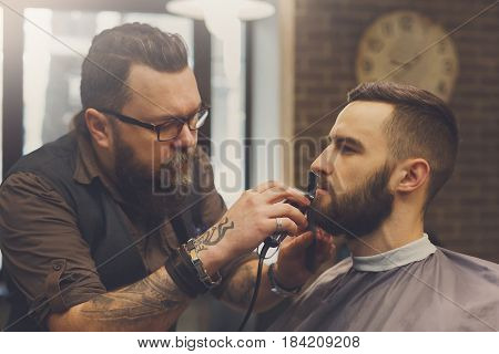 Barber make beard haircut with trimmer hair clipper in barbershop, closeup of client's head. Hairstyle in male hair salon