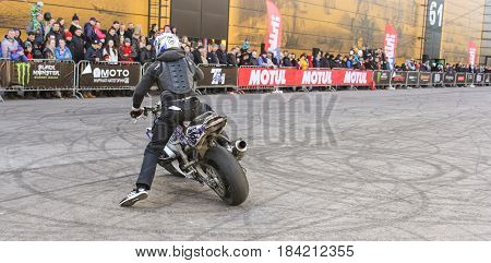 St. Petersburg Russia - 15 April, A biker performing a turn,15 April, 2017. International Motor Show IMIS-2017 in Expoforurum. Sports motorcycle show of bikers on the open area.