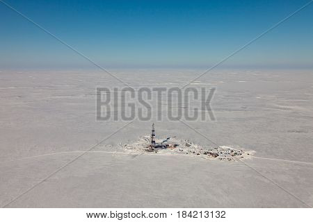 Aerial view of oil rig at an oil field in tundra of Western Siberia in the winter day.