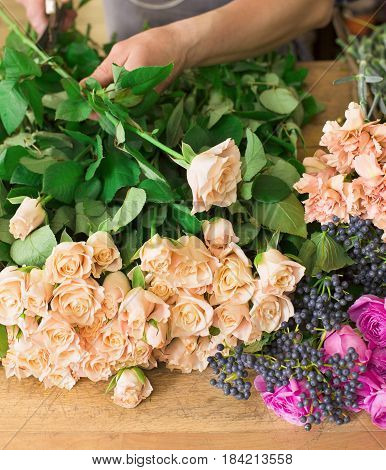 Small business. Male florist hands closeup, cuts rose for bouquet in flower shop. Flowers delivery, creating order