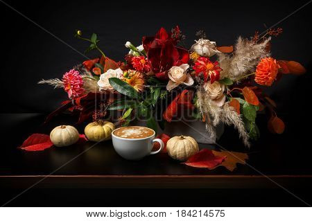 Cappuccino and beautiful flowers still life. Flower shop composition. Coffee cup with foam, apple, fresh and dried flowers bouquet on black wood background. Florist art and floral design concept