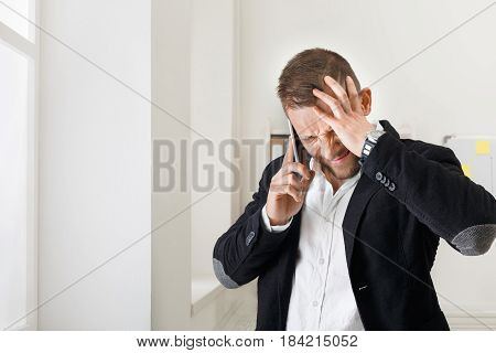 Hard talk. Young stressed businessman makes call with mobile phone near window in modern office. Annoyed, frustrated man, negative emotion. Unpleasant conversation