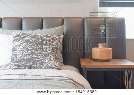 Black And White Pattern Pillows Setting On Bed With Modern Style Reading Lamp