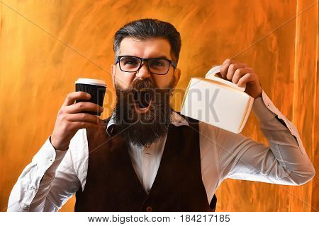 Bearded man long beard. Brutal caucasian unshaven angry hipster with glasses and moustache holding black plastic coffee cup or mug and meal box on brown studio background