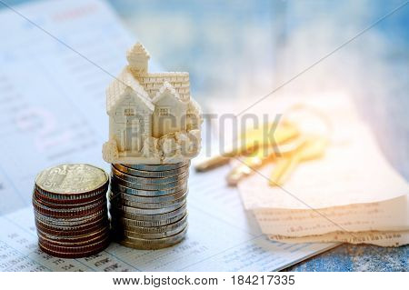 House savings concept,House model and coins on book bank with key house on slip.