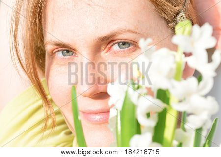 Woman with red hair and freckles and bouquet of white flowers