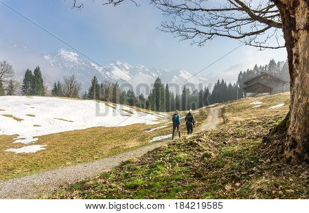 Two female friends enjoying a hike in early springtime with snow covered mountains in background. Reaching a mountain hut for a relaxing rest. Bavaria, Germany, Alps