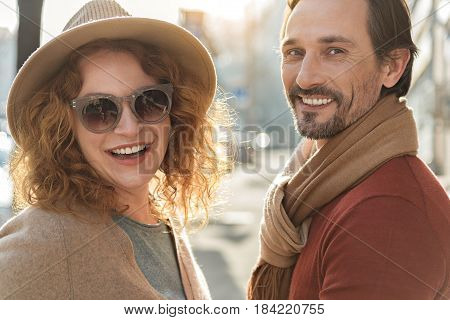Enjoying springtime together. Waist up portrait of joyful man and woman walking on street with pleasure. They are looking at camera and laughing