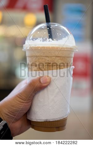 ice coffee frappe with straw in plastic cup on man hand
