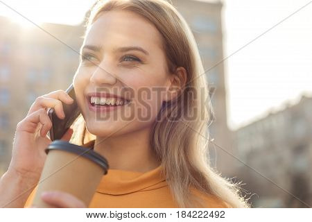Portrait of cute young woman using cellphone for communication. She is drinking coffee and laughing while standing on street