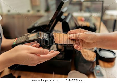Close up of female hand paying for purchase by credit card. Saleswoman is holding device