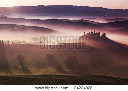 sunlight on foggy hills of Orcia valley Tuscany
