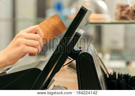 Close up of female hand of cashier keeping credit card under the digital monitor