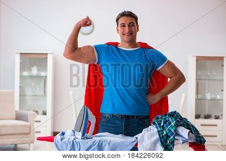 Super hero man husband ironing at home