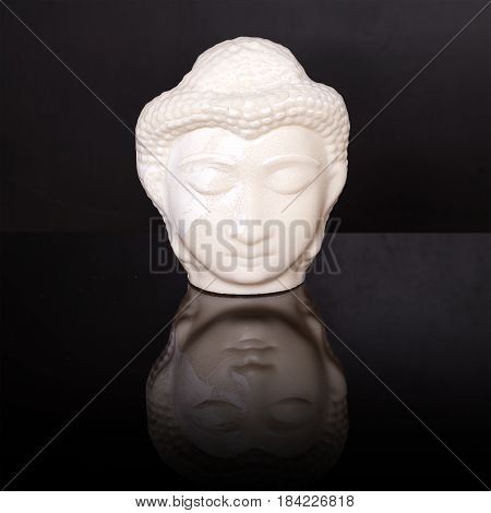Buddha face. Buddha statue made of white marble on black background with reflection. Concept of peace, calm and tranquility. Buddhist artifact for Zen style interior decor