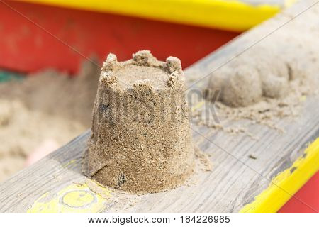 On the railing of the sandbox is a tower of sand. In the background lies another form of sand. On the Playground a square sand box painted in yellow and red.