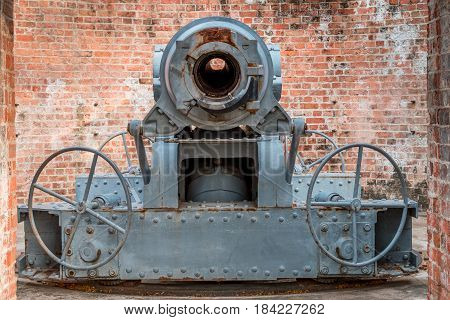 The decommissioned cannon looking through the door made of red brick.