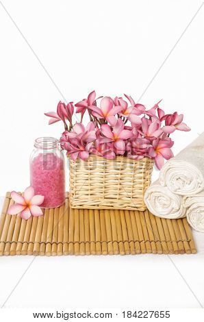 Spa setting with Pink frangipani in basket ,rolled towel, salt in bottle with mat texture