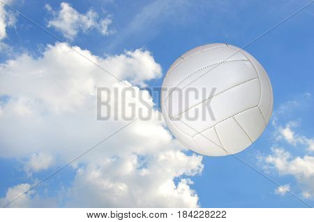 white volleyball airborne in sky with fluffy clouds
