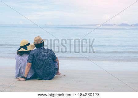Young couple traveler on a tropical beach at Railay beach Krabi Thailand Love couple traveler sitting on beach rear view