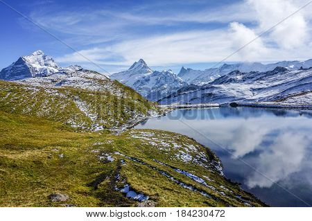 Mountain with snow and green grass with reflection in the lake Autumn daylight Switzerland.
