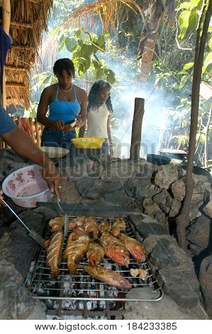 Las Galeras, Dominican Republic - 26 january 2002: woman cooking fish on the outdoor grill at the beach of Rincon near Las Galeras on Dominican Republic