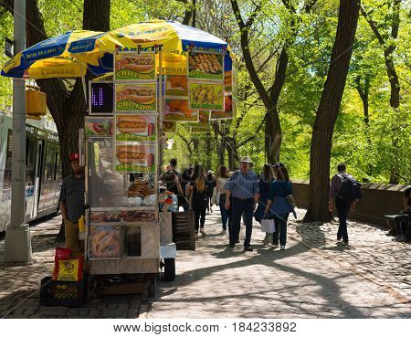 New York NY USA -- April 28 2017 -- A food cart and operator on 5th Avenue's cobblestone sidewalk by New York's Central Park. Editorial Use Only.