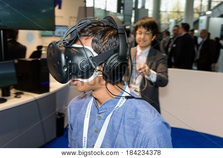 Hannover Germany - March 22 2017: Young man wears the HTC vive vr headset at CeBIT 2017. CeBIT is the world's largest trade fair for information technology.