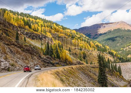 San Juan National Forest USA - October 1 2015: Highway road on mountain with golden aspen trees in Colorado