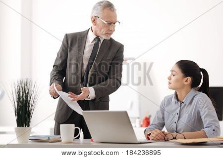 Look here. Attentive brunette sitting in semi position at her workplace looking at documents while being deep in thoughts