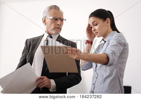 I am also surprised. Shocked girl wrinkling her forehead holding folder with documents standing in semi position