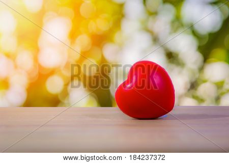 Red heart on wooden table with bokeh light background.