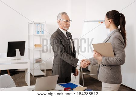 Good deal. Attentive kind employee keeping smile on face standing in semi position while looking at his colleague