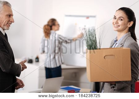 Good work collective. Positive delighted female holding container with her office supplies standing in semi position while looking straight at camera