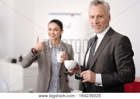 Well criticized. Handsome office worker wearing gray costume holding cup with coffee in right hand while standing in semi position