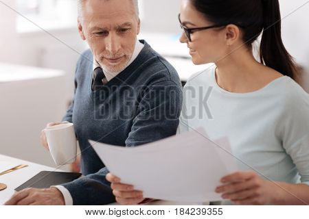 It is my presentation. Attractive smiling office worker putting his hand on the table, going to drink his tea watching new material