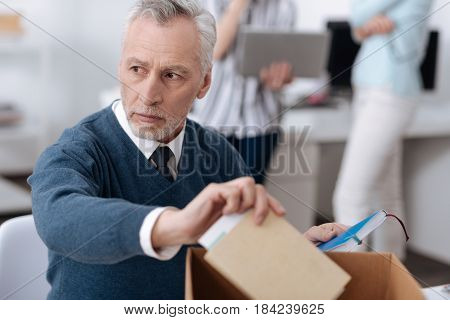 Low spirits. Serious sad bearded male person wearing blue cardigan taking notebook from the box while looking aside