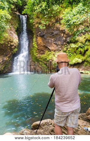 Photographer taking photo of The Chamouze waterfall. Mauritius island