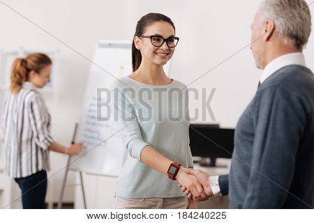 Successful deal. Smiling female wearing smart watches touching hands with her partner while standing opposite him